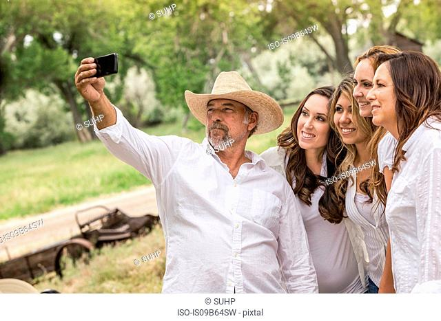 Mature man taking smartphone selfie with women on ranch, Bridger, Montana, USA