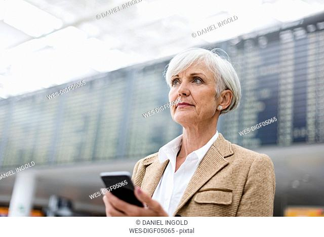 Senior businesswoman holding cell phone at the airport