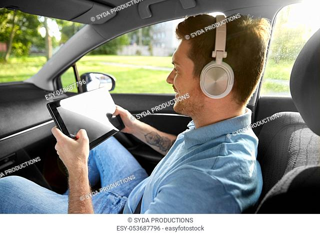 passenger in headphones with tablet pc in taxi car