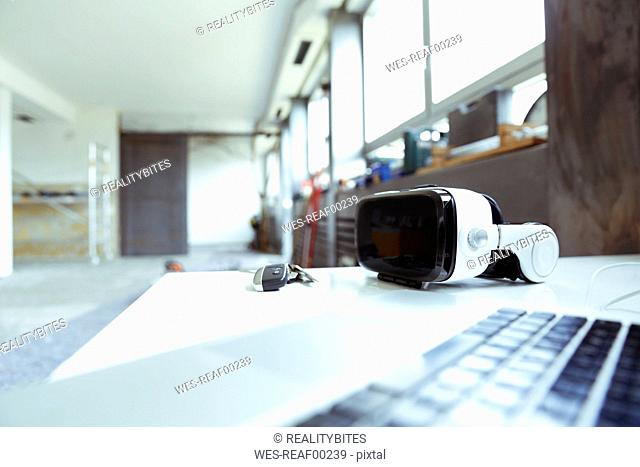 Laptop, keys and Virtual Reality Glasses on table top at construction site
