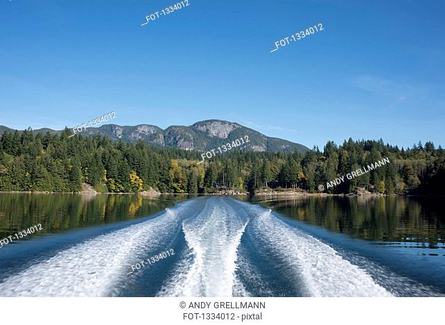 Ferry wakes in lake with mountains in background