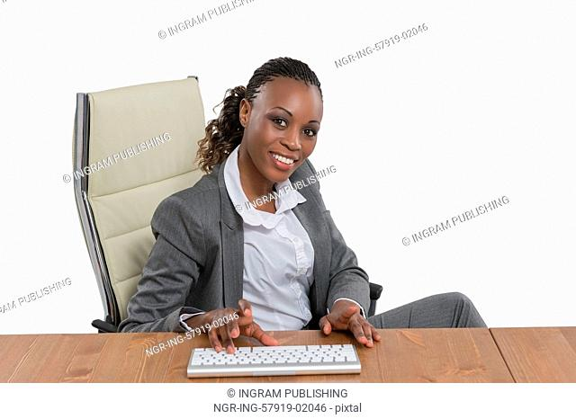 African business woman sitting at her desk and working isolated on white background