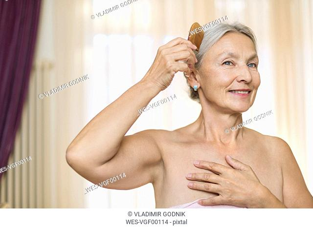 Portrait of smiling senior woman combing her hair in the morning