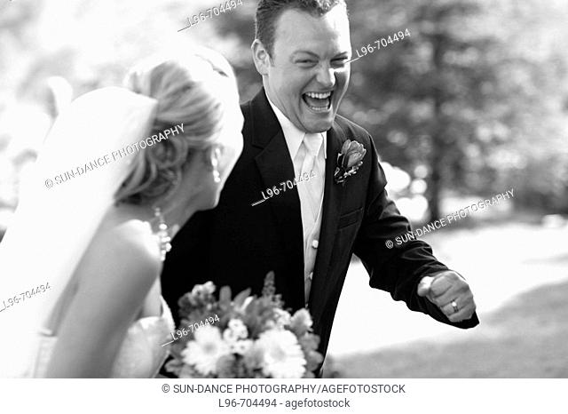 elated groom stealing away with his bride after the wedding ceremony
