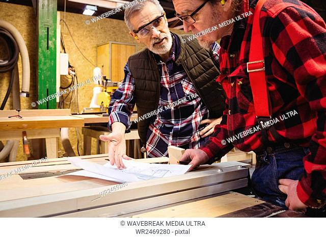 Duo of carpenter working on a wood plank in their workshop