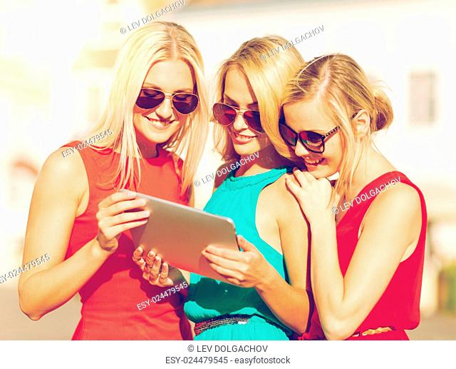 holidays and tourism concept - beautiful blonde girls toursits looking into tablet pc in the city
