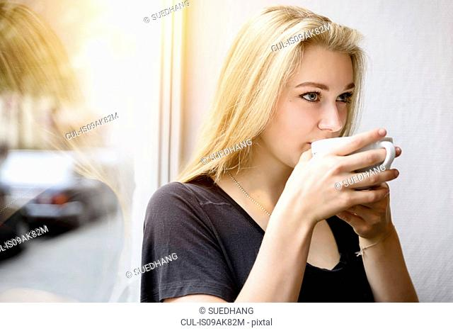 Young woman drinking coffee in window seat