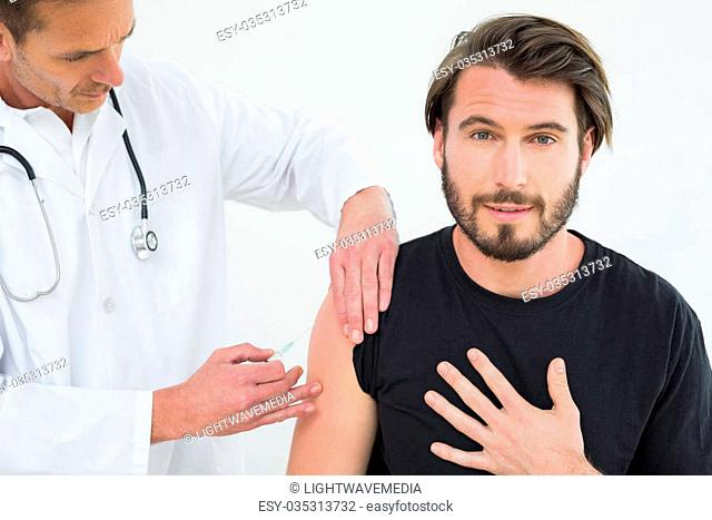 Male doctor injecting a young male patient's arm over white background