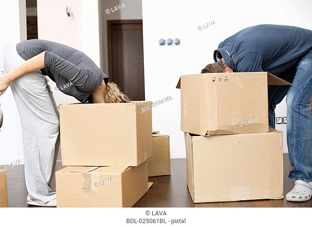 young couple searching for something in moving boxes