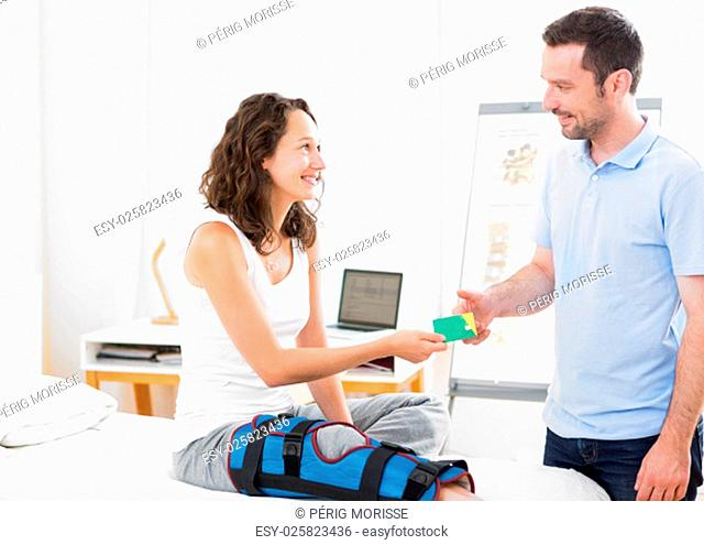 View of a Young attarctive woman giving healthcare card to physiotherapist
