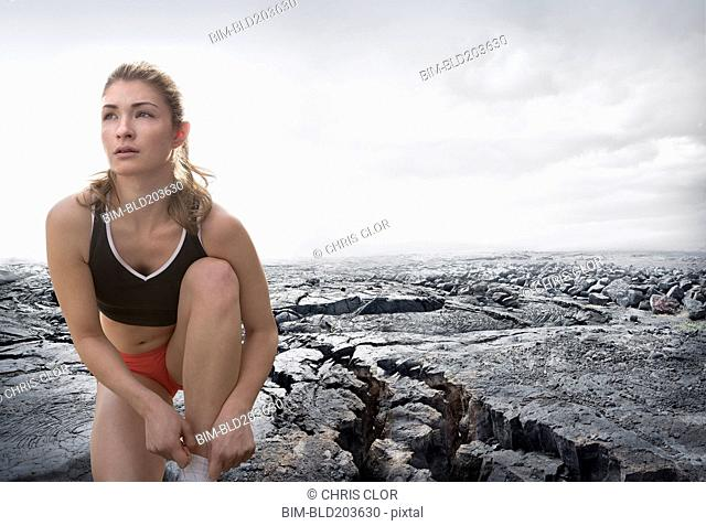Caucasian runner tying shoes on rock formation