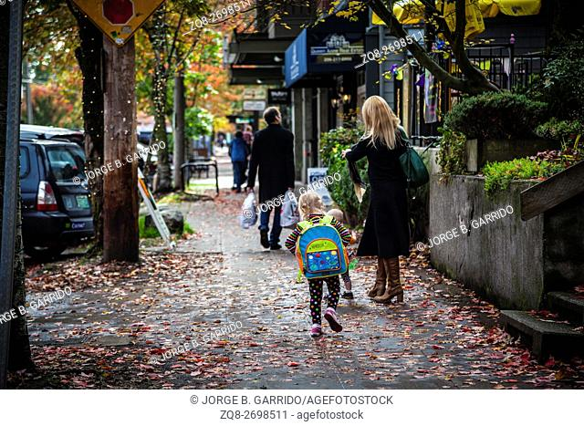 Rear view of schoolgirl walking with mother on pavement, Seattle, Washington state