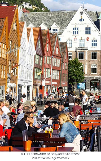 People sitting at outdoor terraces of the pubs at Bryggen, Bergen, Norway