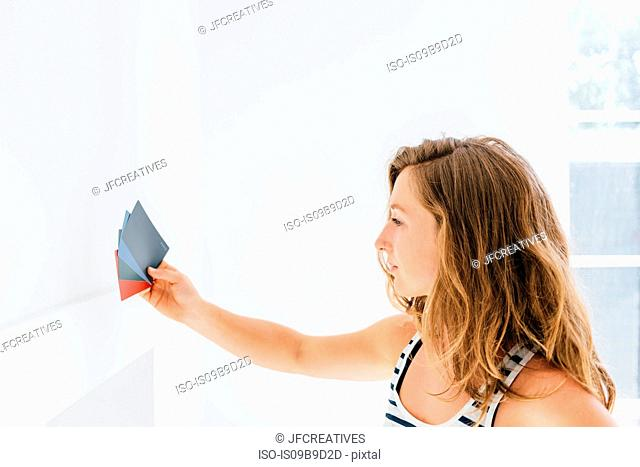 Young woman holding paint swatches against wall