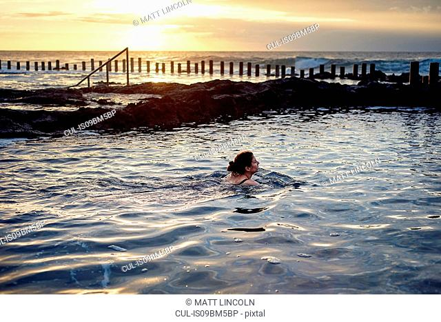 Woman swimming in coastal pool at sunset, Las Palmas, Gran Canaria, Canary Islands, Spain