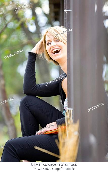 Young woman behind corner laughing loudly