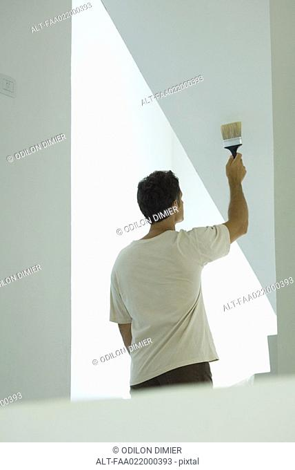 Man painting wall with paintbrush