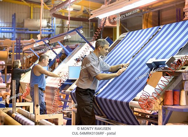 Worker examining loom in textile mill