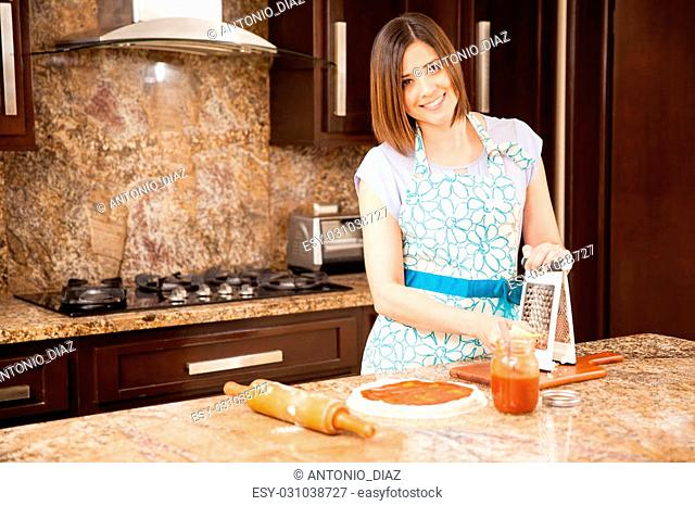 Beautiful young Hispanic housewife grating mozzarella cheese and adding it to her homemade pizza