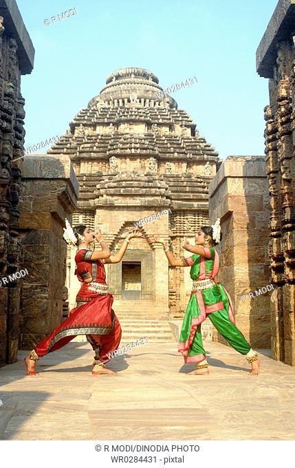 Dancers performing classical traditional odissi dance in front of Konarak Sun temple , Konarak , Orissa , India MR 736D,736C