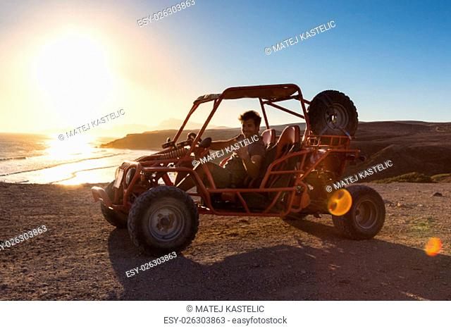 Active man driving quadbike on dirt road by the sea in sunset showing rocking sign to the camera