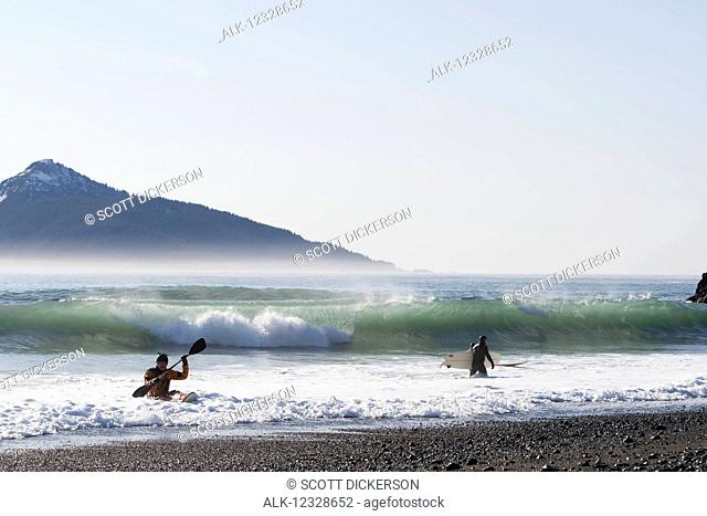 Surfers and kayaking surfer along the Kenai Peninsula Outer Coast, South-central Alaska; Alaska, United States of America