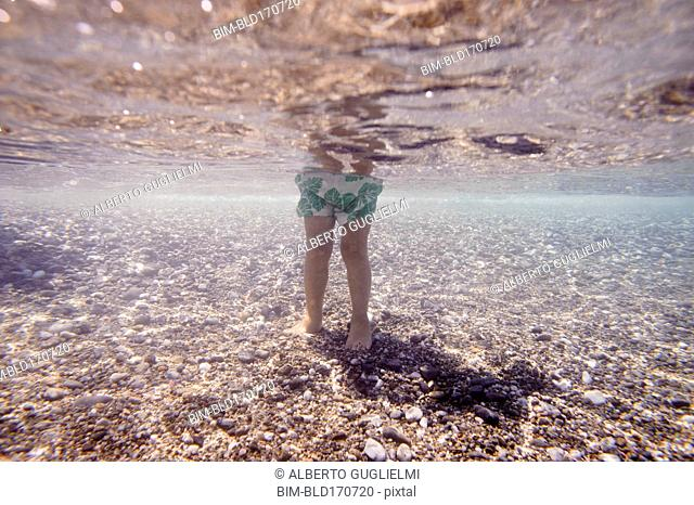 Underwater view of Caucasian girl standing in ocean