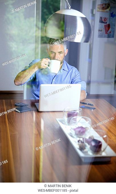Businessman working with laptop at home office drinking coffee
