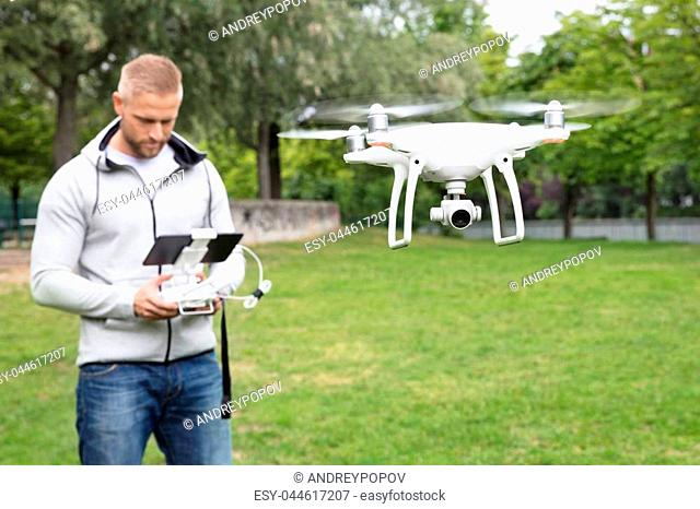 Man Operating The Quadrocopter In The Park
