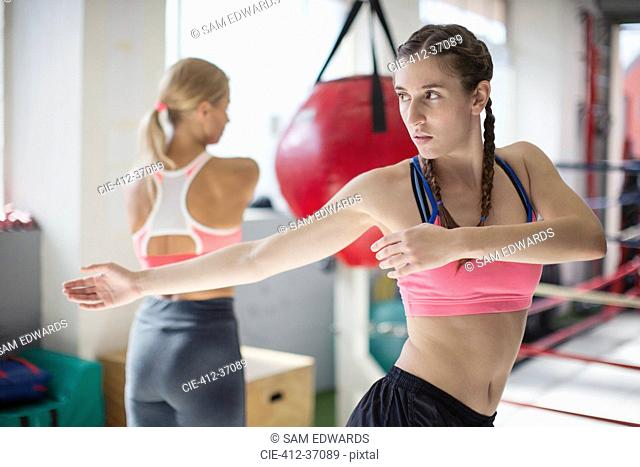 Focused young female boxer stretching, twisting in gym