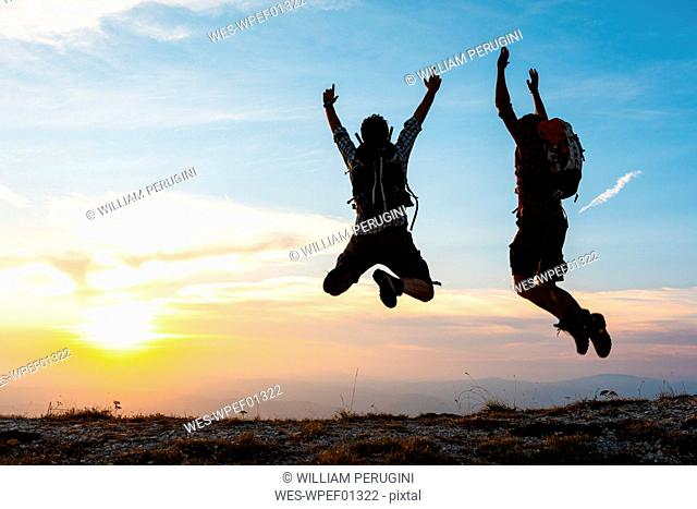 Italy, Monte Nerone, two happy and successful hikers jumping on top of a mountain at sunset