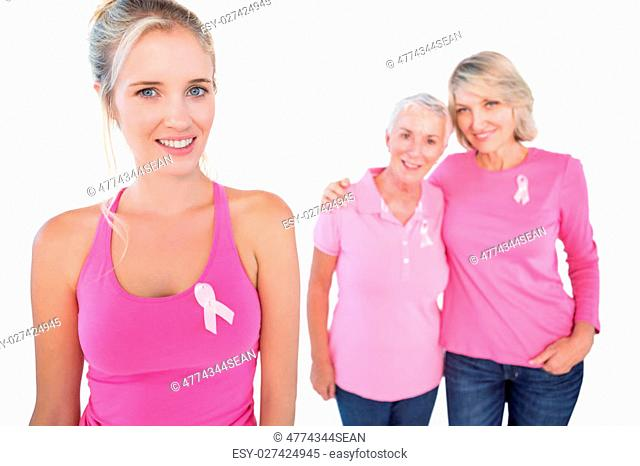 Three happy women wearing pink tops and breast cancer ribbons on white background