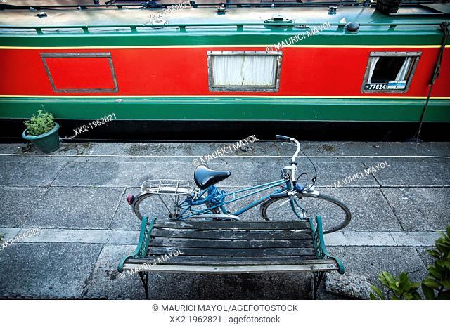 Bike and boat parked next to a bench, Regents canal, London, UK