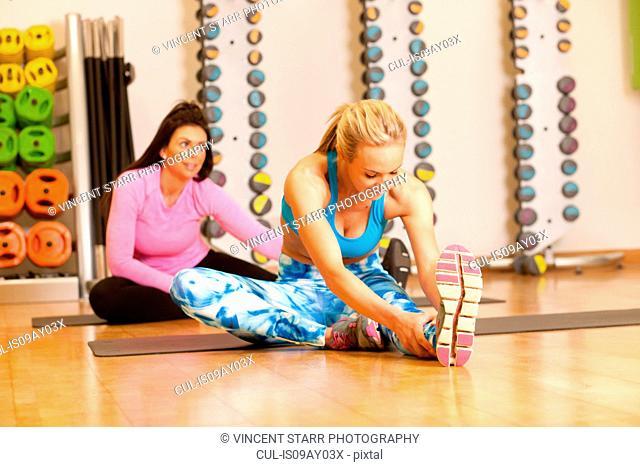Women in gym sitting on yoga mat doing leg stretching exercises