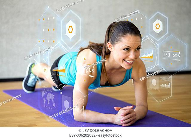 fitness, sport, training, future technology and lifestyle concept - smiling woman doing exercises on mat in gym and graph projection