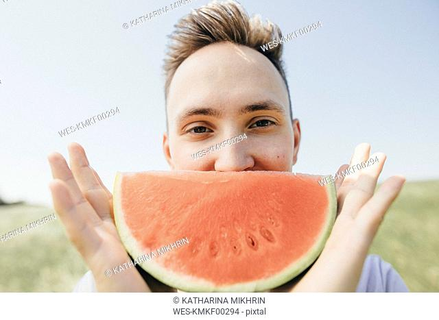 Portrait of a young man holding a watermelon outdoors