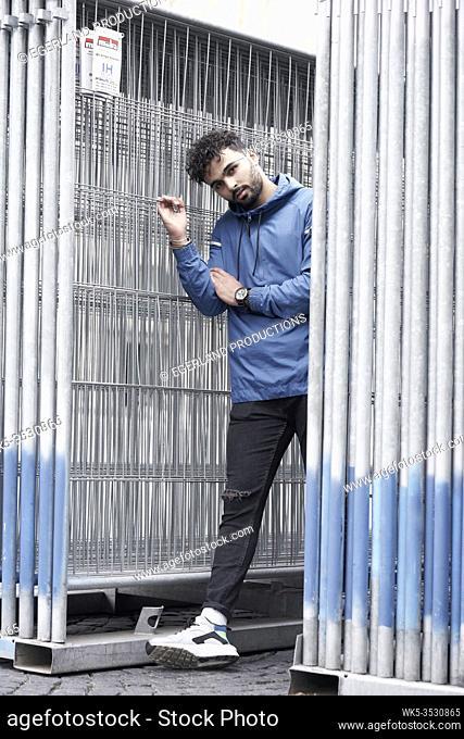 Young man between metal fences