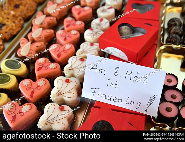 "03 March 2020, Thuringia, Erfurt: """"March 8 is Women's Day"""" is written on a sign between the Petits Fours in a display case at the Confectioners' Day as part..."