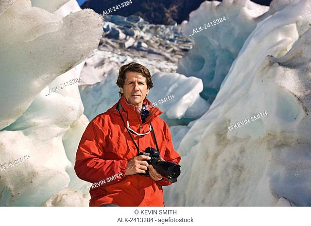 Caucasian middle age male holding a camera and standing in front of Mendenhall glacier near Juneau, Southeast Alaska, USA