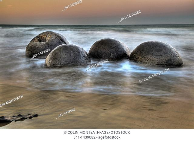Moeraki boulders at dusk, alpenglow over Pacific Ocean, near Oamaru, Otago, New Zealand