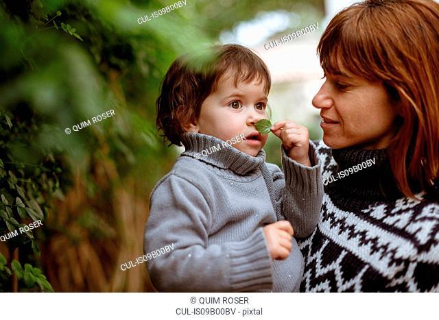 Mother holding daughter, smelling leaf