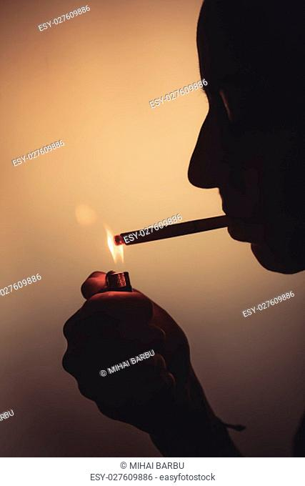 Silhouette of a woman lighting up a cigarette