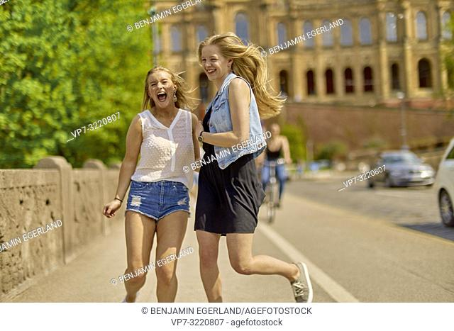 two women running on street, in Munich, Germany