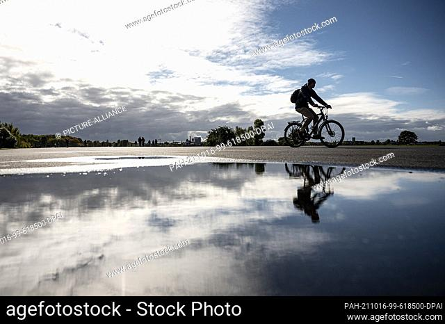 16 October 2021, Berlin: A cyclist is reflected in a puddle on Tempelhofer Feld. Photo: Fabian Sommer/dpa. - Berlin/Berlin/Germany