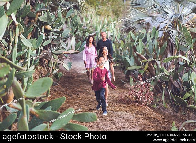 Family of four walking happily on a cactus trail