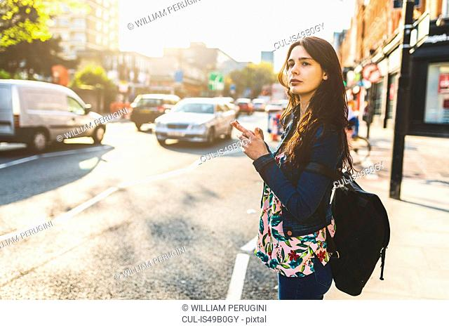 Young woman standing in street, holding smartphone, waiting to cross road