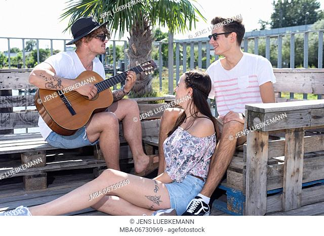 Two young men and a girl outside close guitar