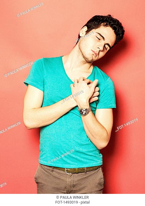 Tired young man sleeping with hands on chest against red background