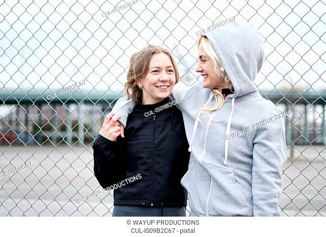 Two female running friends by wire fence