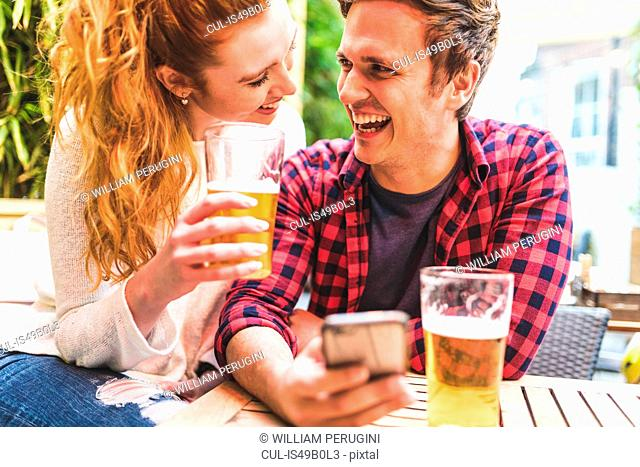 Couple drinking in pub garden, man holding smartphone, laughing